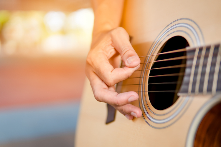 close up of hand playing guitar