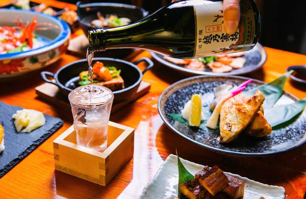 Drink being poured into a shot glass on a table full of Japanese food