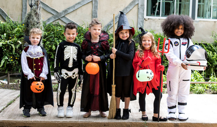 group of kids in halloween costumes holding trick or treat bags