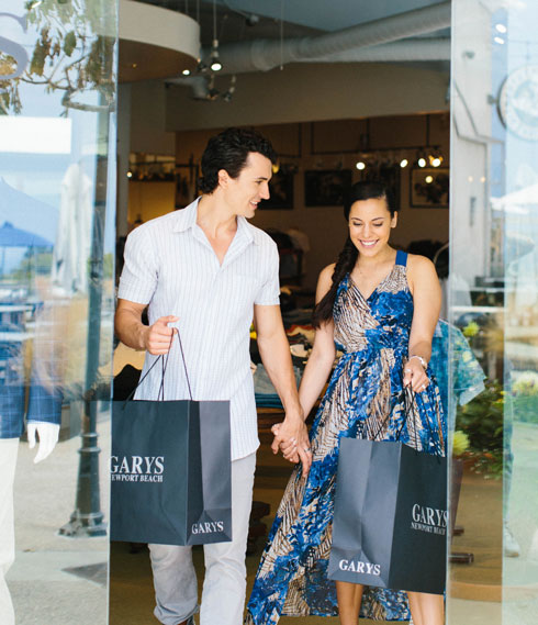 young couple exiting Del Mar Plaza shop holding hands and shopping bags