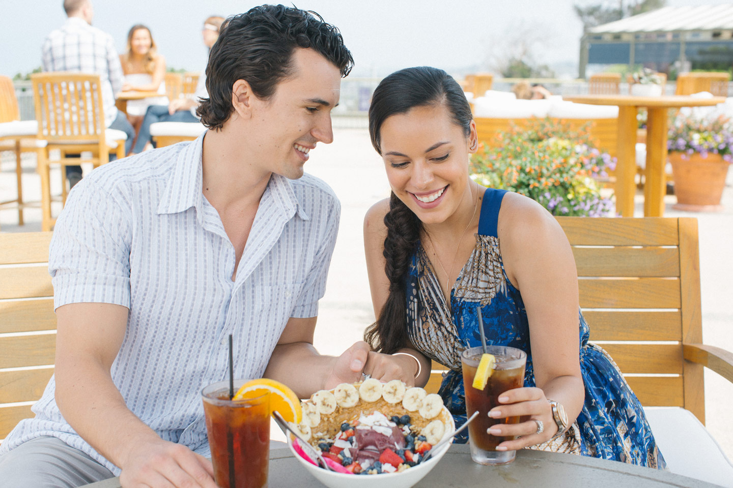 young couple smiling and enjoying food and drinks at del mar plaza
