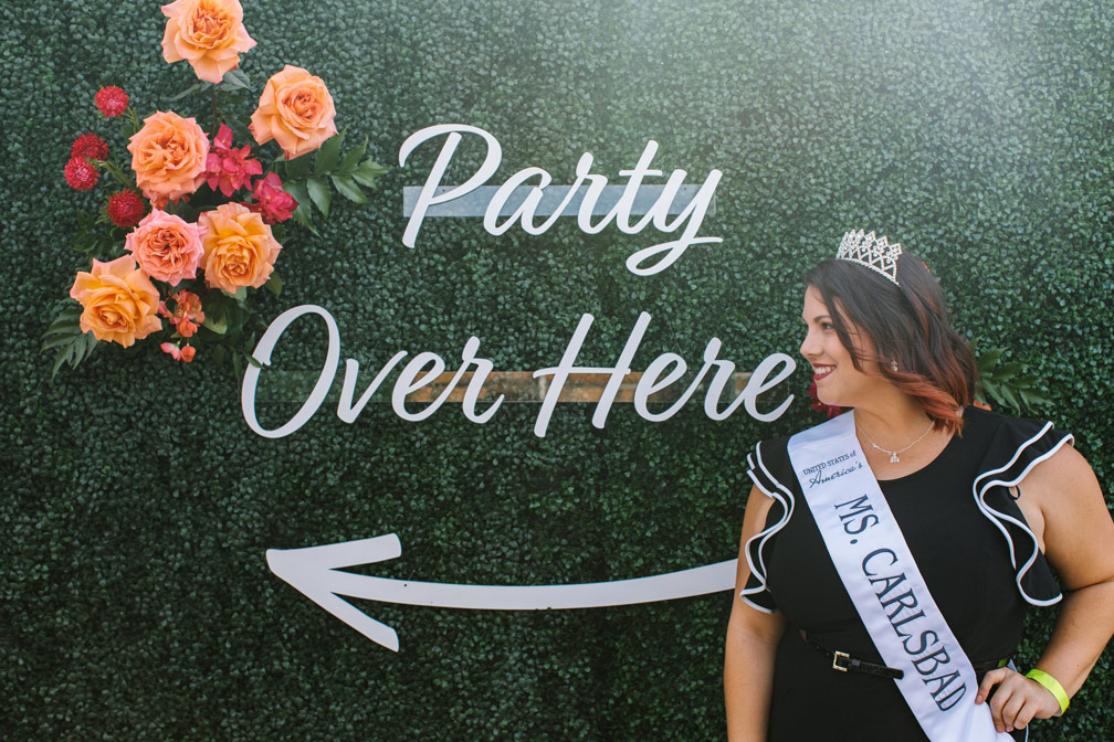 woman wearing a tiara and 'ms. carlsbad' sash standing in front of sign with flowers that says 'party over here'