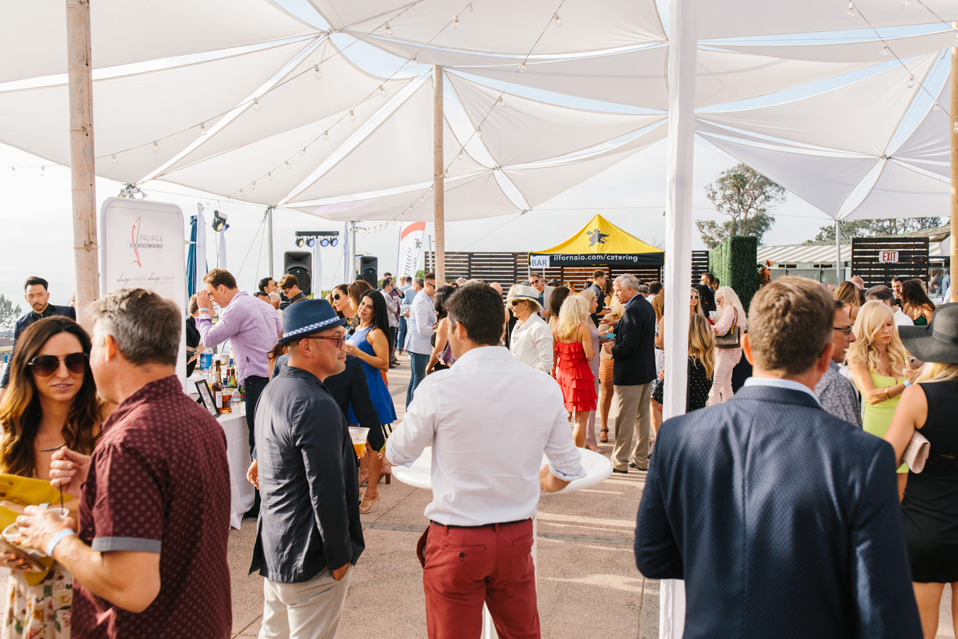 happy guests mingle under tent at del mar plaza